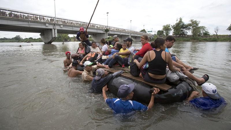 Một nhóm người di cư Trung Mỹ dùng bè vượt sông Suchiate để vào Mexico, tại TP Ciudad Hidalgo (Mexico). Ảnh: AP