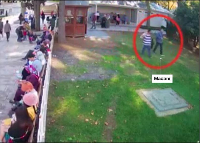 4 giờ 29 phút chiều 2-10: Ông Madani (bên phải, trong vòng tròn) mặc lại quần áo cũ của mình. Người đồng sự đã cởi áo khoác ngoài, tay mang một túi nhựa được cho đựng quần áo nhà báo Khashoggi. Ảnh: CNN