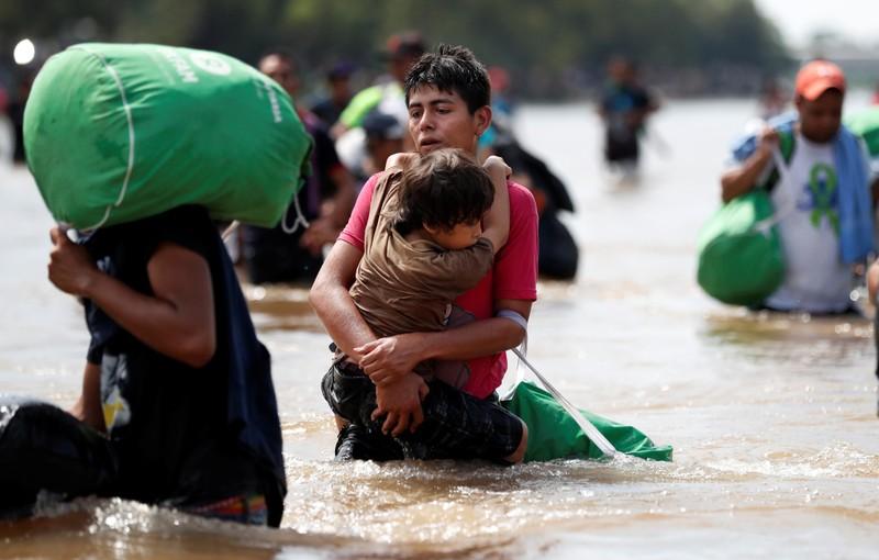 Đoàn người di cư Trung Mỹ vượt sông ở Mexico trên đường tiến về biên giới với Mỹ. Ảnh: REUTERS