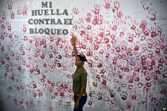 Một phụ nữ đứng trước bức tranh vẽ tường ở Havana (Cuba) ngày 31-10 nhân sự kiện vận động phản đối lệnh cấm vận kinh tế của Mỹ với Cuba. Ảnh: AP