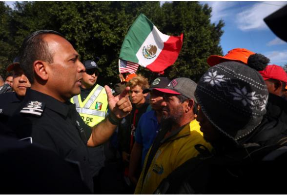 Người di cư Trung Mỹ va chạm với cảnh sát Mexico ở khu vực cửa khẩu El Chaparral, TP Tijuana (Mexico) giáp biên giới TP San Diago, bang California (Mỹ) ngày 22-11. Ảnh: REUTERS