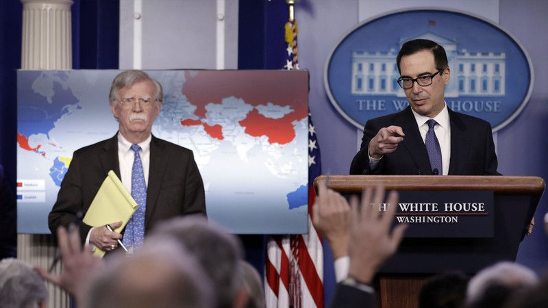 Bộ trưởng Tài chính Mỹ Steven Mnuchin (phải) và Cố vấn an ninh quốc gia Mỹ John Bolton (trái) thông báo trừng phạt tập đoàn dầu khí quốc gia Venezuela PDVSA ngày 28-1. Ảnh: AP