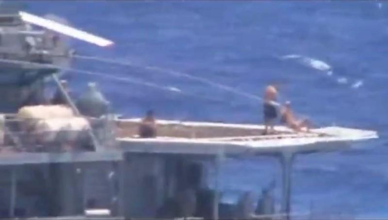 Thủy thủ Nga được cho là đang tắm nắng trên khu vực đậu trực thăng của tàu khu trục Đô đốc Vinogradov lớp Udaloy của Nga. Ảnh: US NAVY