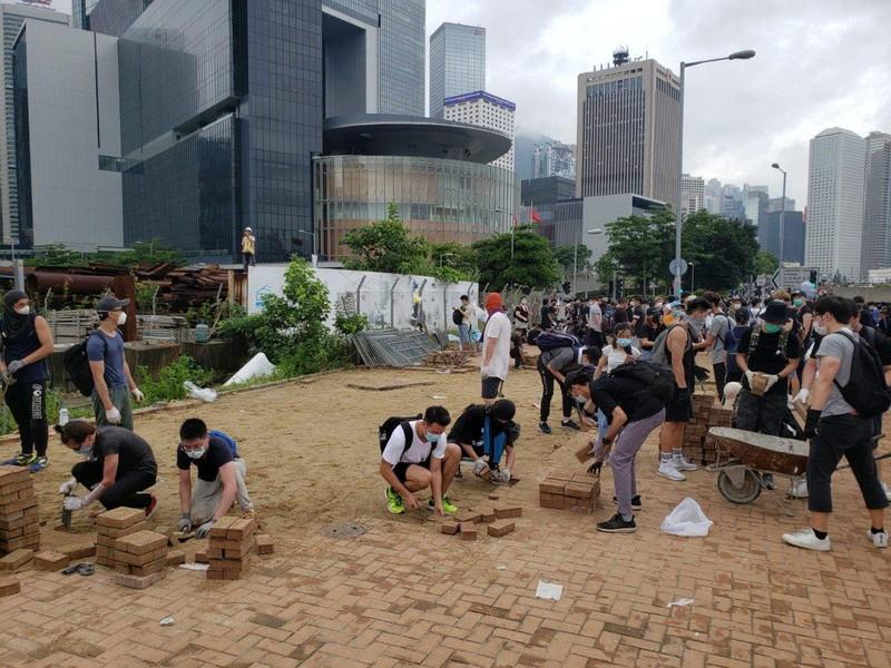 Người dân gỡ gạch lát vỉa hè dựng tường đối phó cảnh sát. Ảnh: SCMP