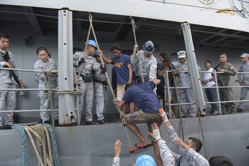 Ngư dân Philippines được chuyển lên một tàu khác để vào bờ. Ảnh: AP