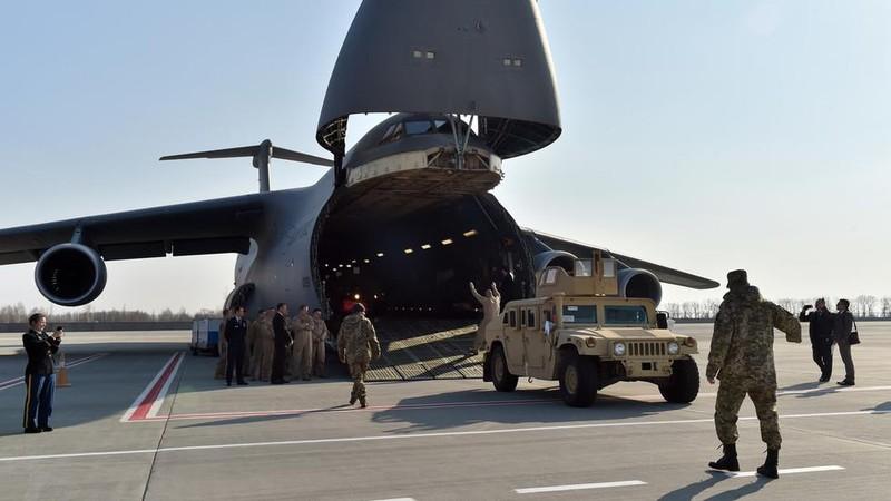 Quân nhân Ukraine và quân nhân Mỹ dỡ xe bọc thép từ một máy bay vận tải quân sự tại sân bay Kiev. Ảnh: AFP