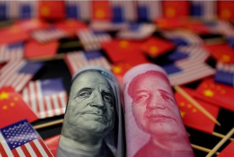 Đồng USD của Mỹ (trái) và đồng Nhân dân tệ của Trung Quốc (phải). Ảnh: REUTERS