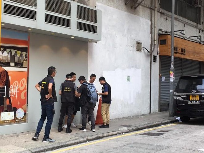 Cảnh sát tiếp cận kiểm tra giấy tờ tùy thân và tư trang thanh niên Hong Kong trên đường phố. Ảnh: SCMP