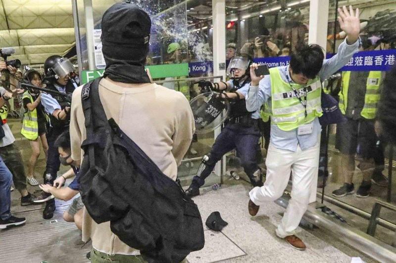 Một cảnh sát (phải) thực hiện nhiệm vụ can thiệp biểu tình tại sân bay ngày 13-8. Ảnh: SCMP