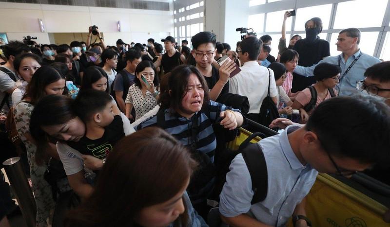 Hành khách bật khóc trong khi cố len lỏi qua đám đông tại sân bay. Ảnh: SCMP