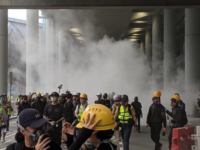 Người biểu tình cướp vòi rồng phun nước bên ngoài nhà ga sân bay. Ảnh: SCMP