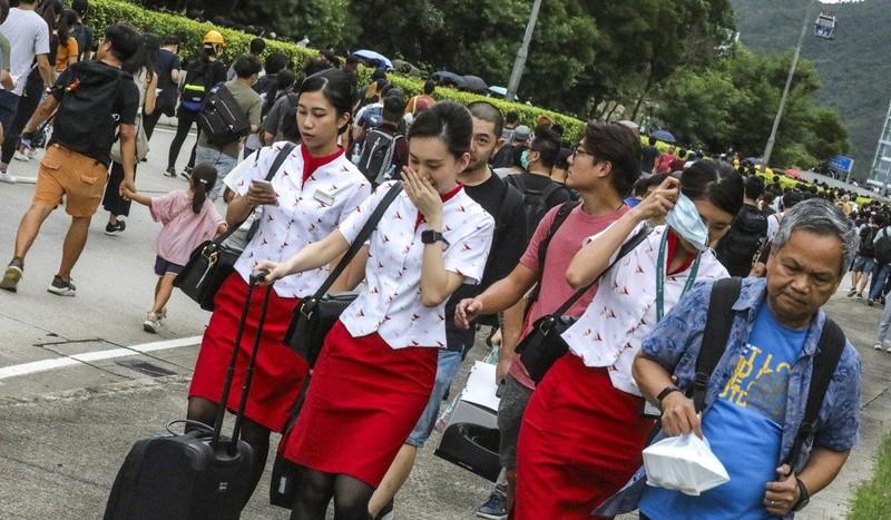 Hành khách và phi hành đoàn kéo hành lý đi bộ về sân bay. Ảnh: SCMP