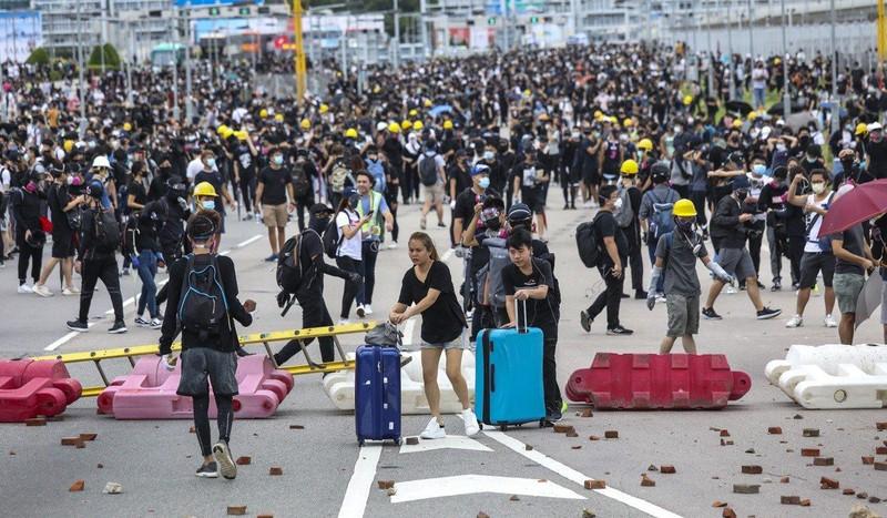 Hành khách phải kéo hành lý đi bộ trên đường quốc lộ để đến sân bay vì giao thông bị người biểu tình phong tỏa trong cuộc biểu tình ngày 1-9 tại Hong Kong. Ảnh: SCMP