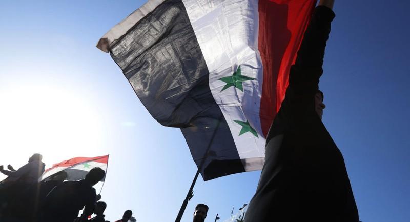 Người ủng hộ chính phủ Syria cầm cờ quốc gia Syria trong một cuộc biểu tình phản đối phương Tây, sau khi Mỹ-Anh-Pháp cùng không kích Syria với lý do nước này sử dụng vũ khí hóa học chống lại dân thường, tháng 4-2018. Ảnh: SPUTNIK