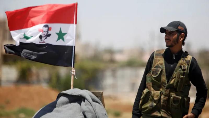 Binh sĩ quân đội Syria đứng gần cờ quốc gia Syria ở TP Deraa, tây nam Syria tháng 7-2018. Ảnh: REUTERS
