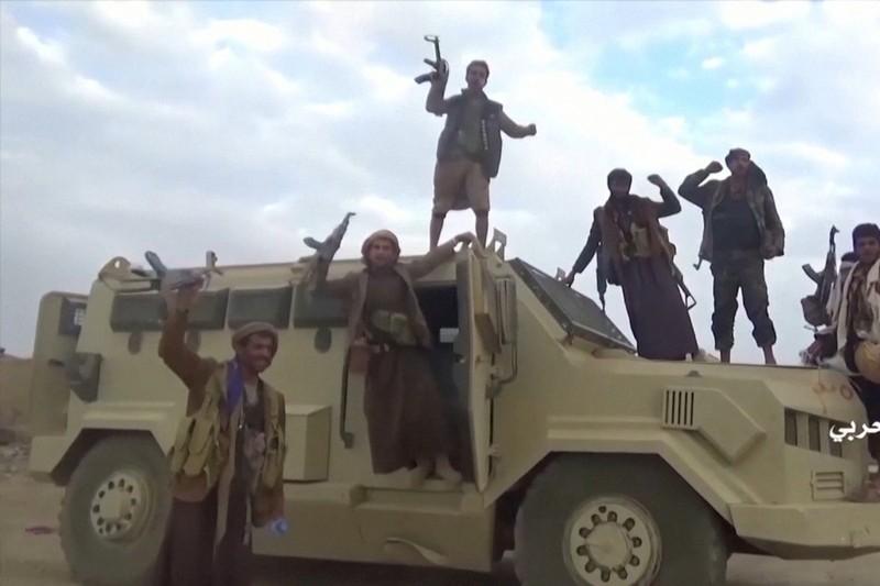 Các tay súng Houthis bên cạnh một xe quân sự của Saudi Arabia. Ảnh: REUTERS
