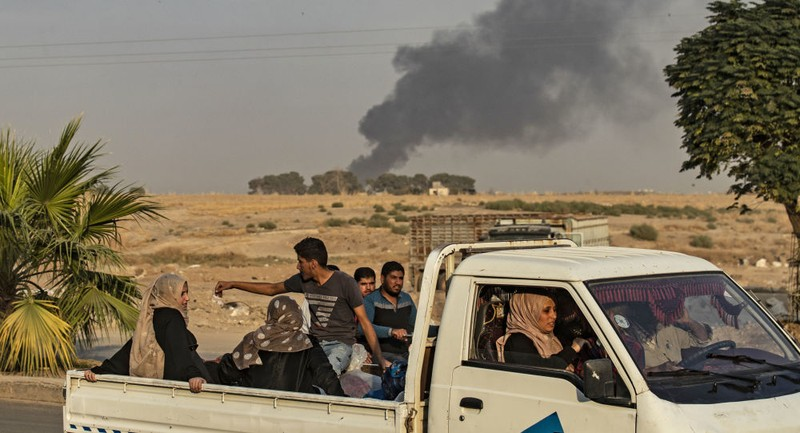 Người dân Syria ở TP Ras al-Ain thuộc tỉnh al-Hasakah (Syria) giáp biên giới với thổ Nhĩ Kỳ sơ tán ngày 9-10. Ảnh: AFP