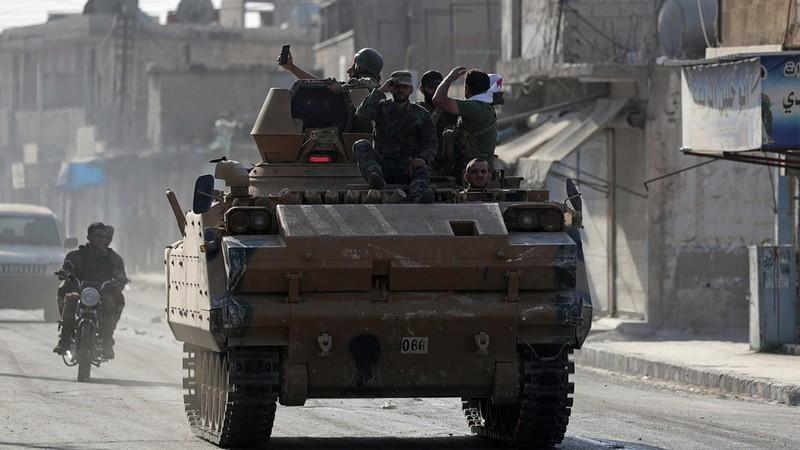 Lực lượng tay súng Syria được Thổ Nhĩ Kỳ bảo trợ di chuyển trên đường quốc lộ M4 qua thị trấn Tell Abyad, tỉnh Raqqa ở bắc Syria. Ảnh: REUTERS