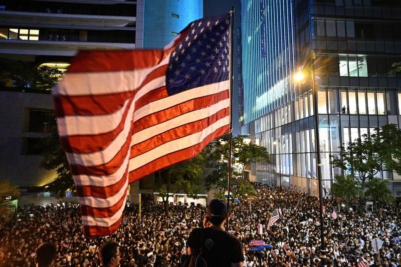 Người biểu tình giương cờ Mỹ trong cuộc biểu tình ngày 14-10 tại Hong Kong. Ảnh: AFP