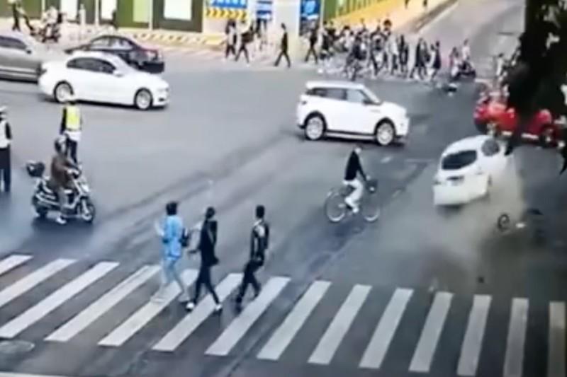 Từ hình ảnh từ máy quay giám sát an ninh có thể thấy một chiếc ô tô màu trắng được điều khiển vượt đèn đỏ và tông phải một phương tiện khác trong sự hốt hoảng của rất nhiều người đi đường. Ảnh: SCMP