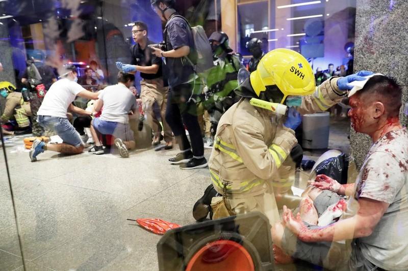 Một lính cứu hỏa sơ cứu cho nghi can thực hiện vụ tấn công, trong khi nhiều người khác giúp đỡ những người bị thương trong vụ tấn công. Ảnh: SCMP