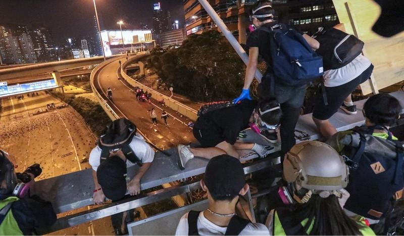 Người biểu tình đu dây thoát từ một cây cầu đi bộ xuống đường và được xe máy chở đi. Ảnh: SCMP