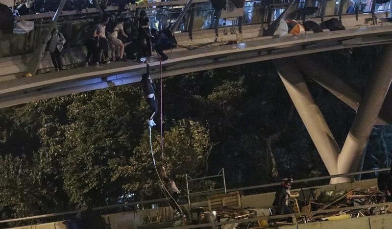 Người biểu tình đu dây từ cây cầu đi bộ xuống con đường bên dưới thoát ra khỏi trường, khuya 18-11. Ảnh: SCMP