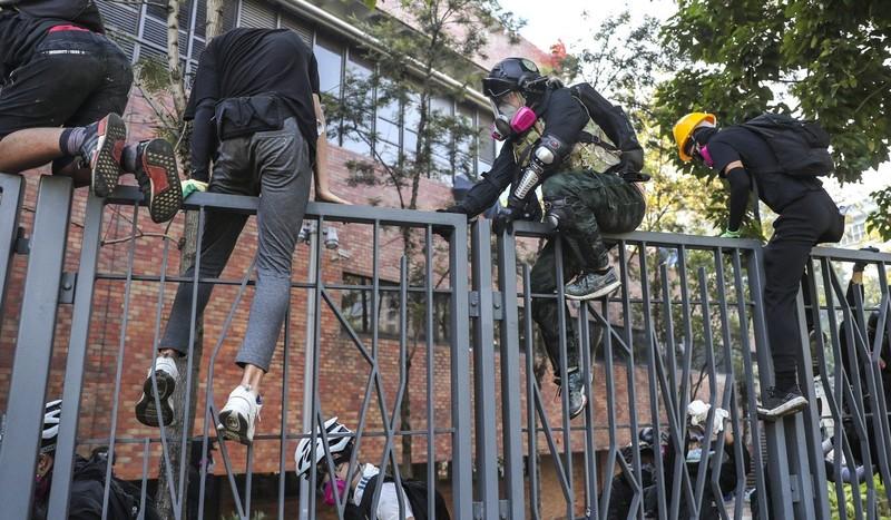 Nhiều sinh viên trèo hàng rào cố gắng rời trường. Ảnh: SCMP