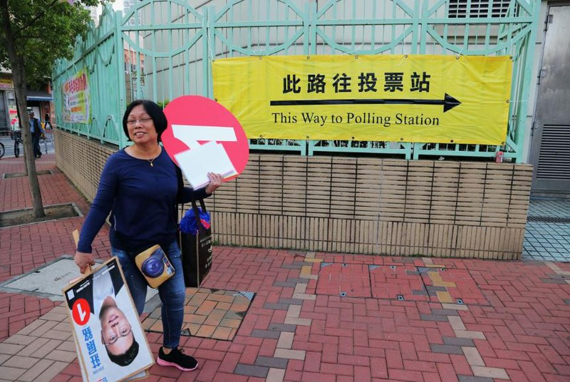 Một phụ nữ vận động cho một ứng viên bên ngoài một địa điểm bỏ phiếu trong cuộc bầu cử địa phương ở Hong Kong sáng 24-11. Ảnh: REUTERS