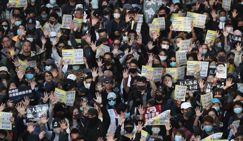 Người biểu tình giơ tay thể hiện biểu tượng 5 yêu cầu của mình. Ảnh: SCMP