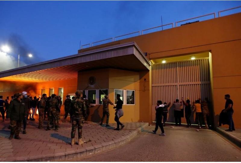 Các tay súng nhóm vũ trang Kata'ib Hezbollah và người biểu tình Iraq tập trung bên ngoài trụ sở đại sứ quán Mỹ ở Baghdad (Iraq) ngày 31-12. Ảnh: REUTERS