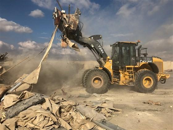 Xe ủi đất được triển khai dọn dẹp các đống đổ nát ở căn cứ không quân Ayn al-Asad ngày 13-1. Ảnh: AP
