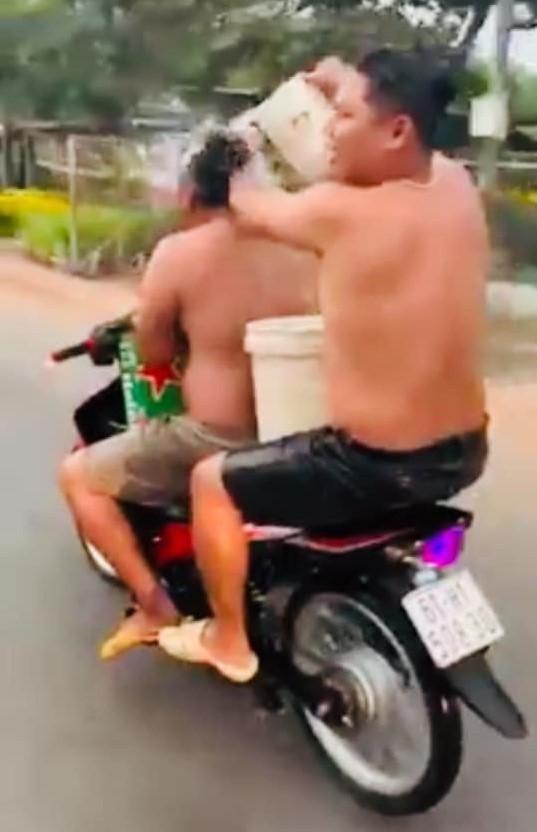Vừa chạy xe vừa tắm, hai thanh niên bị công an phạt nặng - ảnh 1