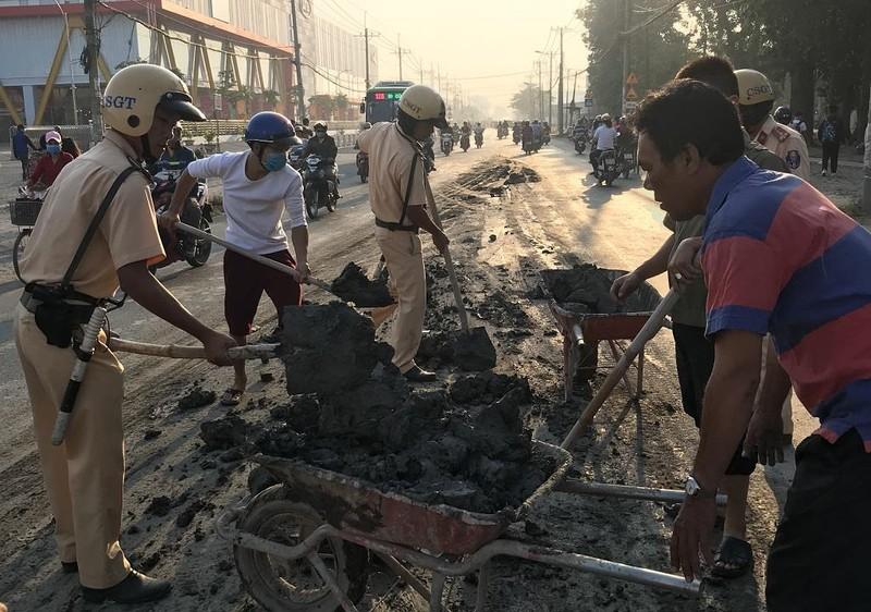 CSGT đẩy xe cút kít đổ bùn đất cho dân khỏi trượt - ảnh 1