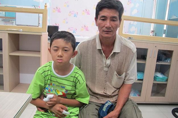 Cháu Tú và cha tại Bệnh viện Mắt TP.HCM - Ảnh: Thùy Dương