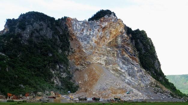 Từ một ngọn núi rất đẹp trên tuyến quốc lộ 12A, núi Cây Trỗ (xã Thạch Hóa, huyện Tuyên Hóa) đã tan nát sau hơn một năm được cấp phép khai thác đá xây dựng - Ảnh: Quốc Nam