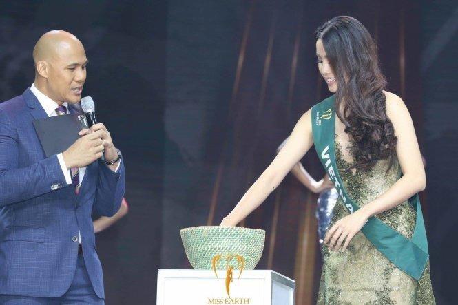 Nam Em bốc thăm câu hỏi thi ứng xử tại chung kết Miss Earth. Ảnh TTO