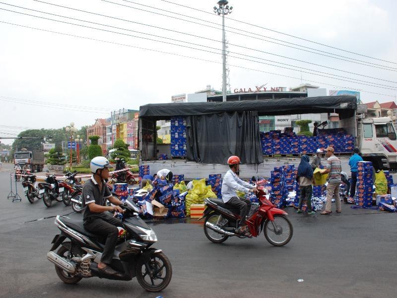Xe tải chở bia bung thùng, người dân gom giúp tài xế - ảnh 1