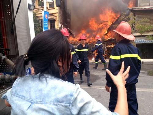 Lửa cháy dữ dội trong khi khá nhiều lính cứu hỏa đứng phía ngoài. Ảnh: Trần Hải.
