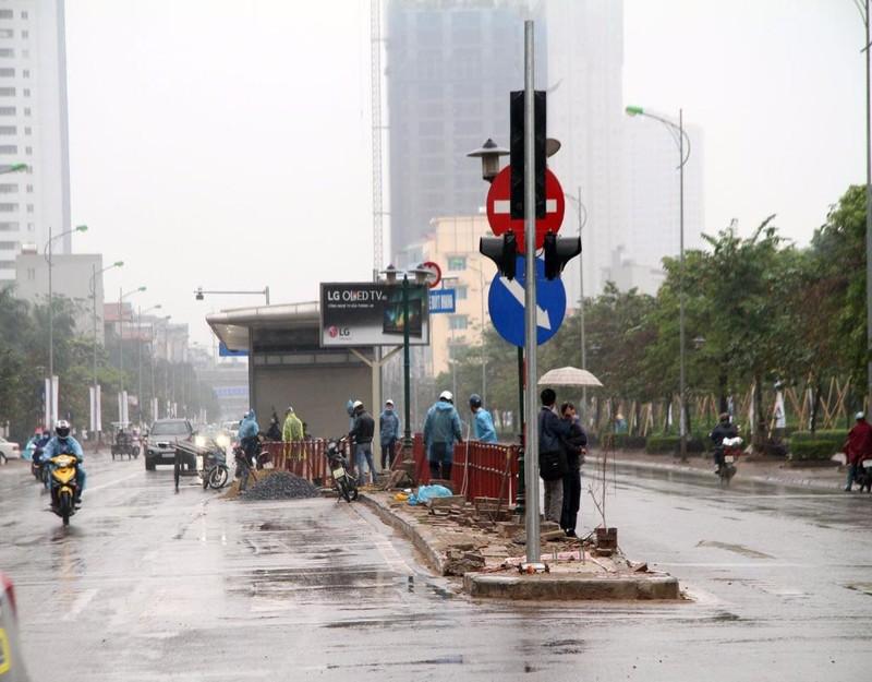 Tại một điểm khác trên đường Lê Trọng Tấn, các công nhân vẫn đội mưa để hoàn thiện nốt các công trình phụ của nhà chờ.