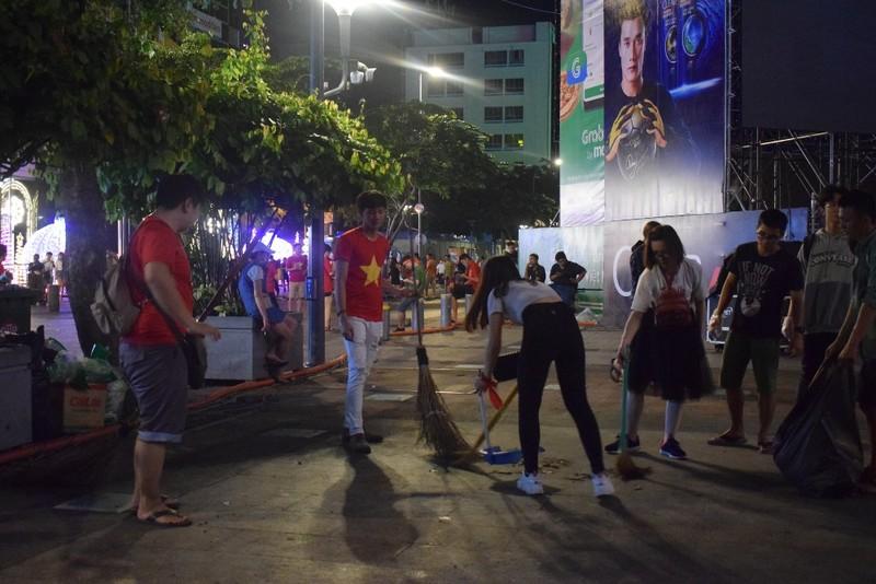 Những người trẻ lặng lẽ ở lại phố đi bộ Nguyễn Huệ dọn rác  - ảnh 1