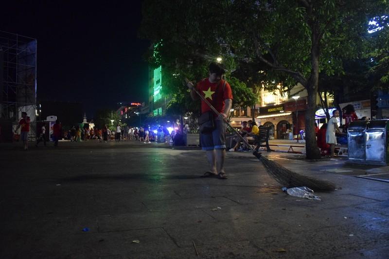 Những người trẻ lặng lẽ ở lại phố đi bộ Nguyễn Huệ dọn rác  - ảnh 3