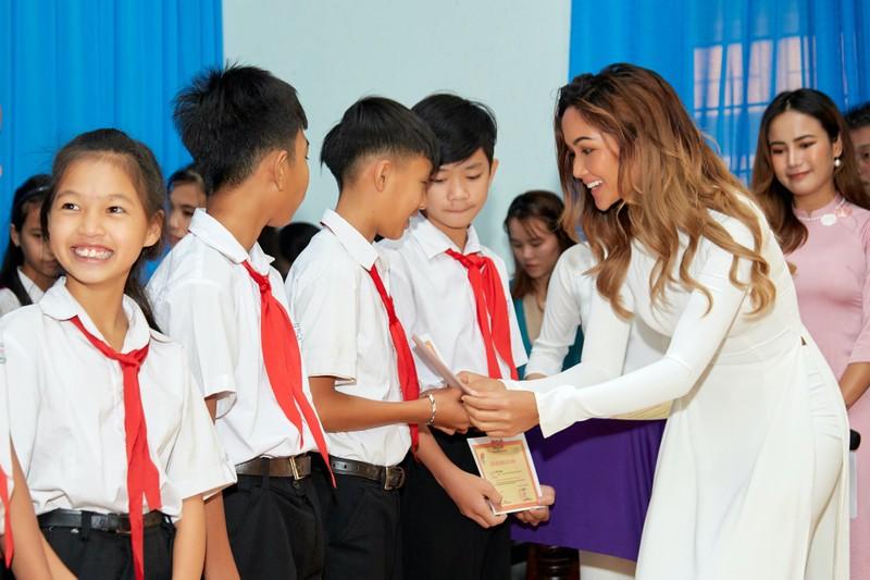 Hoa hậu H'Hen Niê giản dị áo dài trắng về thăm trường cũ - ảnh 1