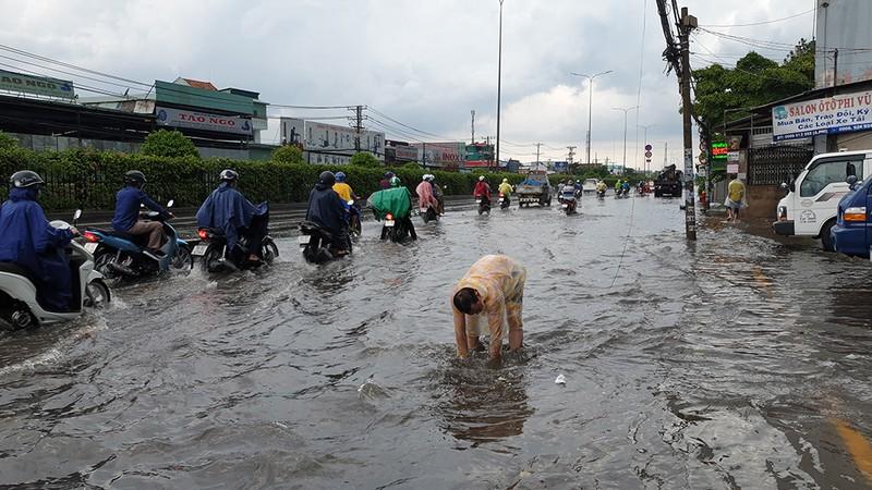 Mưa lớn, đường ngập, người dân hối hả đi móc cống - ảnh 1