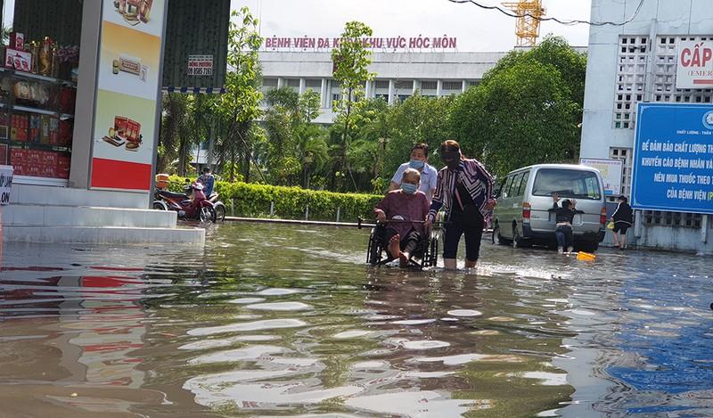 Mưa lớn, đường ngập, nước cống tràn vào Bệnh viện Hóc Môn - ảnh 1