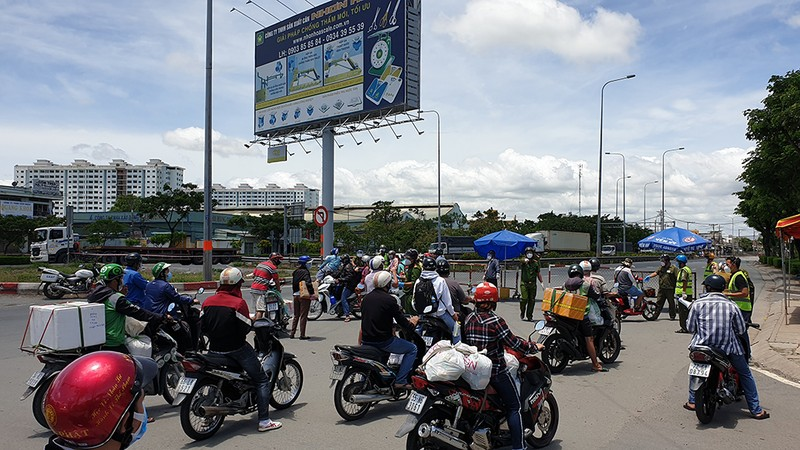 Tại khu vực chốt, rất đông người đi xe máy được lực lượng chức năng yêu cầu quay đầu, chọn lộ trình khác. Ảnh: NT