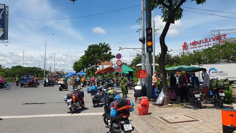 Khu vực chốt chặn ở trên quốc lộ 1 đoạn qua địa bàn xã Tân Kiên, huyện Bình Chánh tập trung khá đông người dân miền Tây đang tìm đường về quê. Ảnh: NT