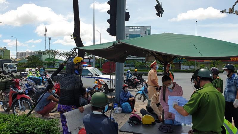 Lực lượng chức năng giải thích, vận động với người dân quay trở lại vì việc đi xe máy để về quê là điều không thể. Ảnh: NT