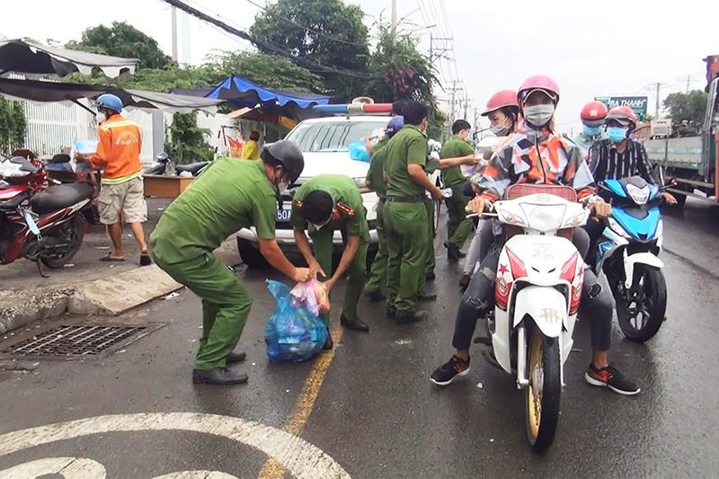 Tháo dỡ chốt ở thị trấn Tân Túc, công an phát nước, bánh mì cho người về quê - ảnh 3