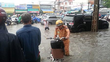 Cảnh sát giao thông Biên Hòa giúp dân trong cơn mưa lớn - ảnh 1